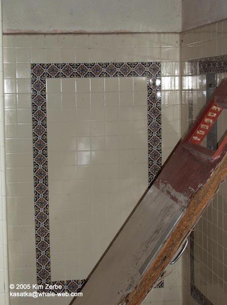 Part of the shower wall with a broken door